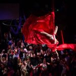 Shot of upside down aerialist with red silks above an amazed audience
